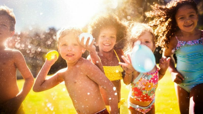niños y niñas jugando a globos de agua